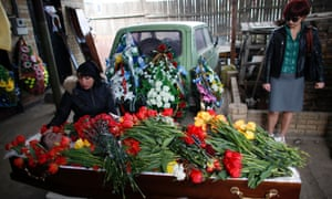 The wife of Donetsk deputy Vladimir Rybak mourns next to his coffin during a funeral in the village of Horlivka, in eastern Ukraine.