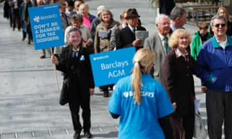 A demonstrator wearing a mask depicting Barclays Chief Executive Antony Jenkins in the shareholder queue.