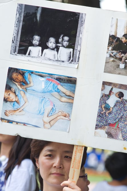 A woman holds up a poster with photos from an internment camp in North Korea during a White House vigil