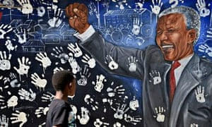 A boy walks past a mural painted outside a house where Nelson Mandela once lived, in Johannesburg