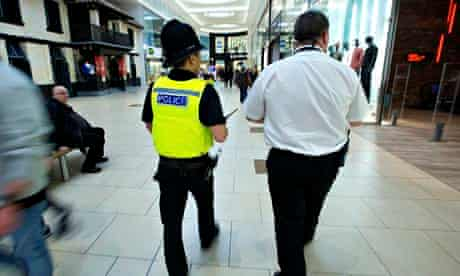 Police officer and security operative patrol a shopping centre