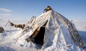 Natasha Nomro, a Chukchi woman, scraping snow from the top of her reindeer skin Yaranga at a  herders' winter camp on the tundra. Chukotskiy Peninsula, Chukotka, Siberia, Russia