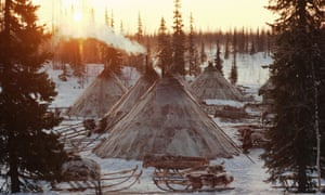 Sun rises behind reindeer skin tents at a winter camp of a group of Nenets herders. Yamal.