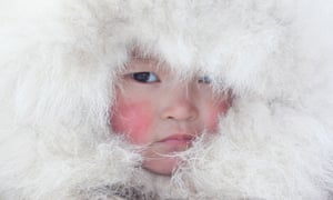 Nenya Vanuito, a young Nenets girl, wearing a traditional hat with fur trim at a winter camp near Tambey. Yamal Peninsula, Western Siberia, Russia.