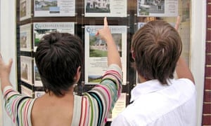 FIRST TIME PROPERTY BUYERS LOOKING AT ESTATE AGENTS WINDOW