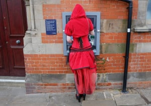 A woman dressed a Little Red Riding Hood withdraws money from a cashpoint.