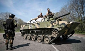 Ukrainian soldiers sit on top of an armoured personnel carrier at a checkpoint outside Slaviansk