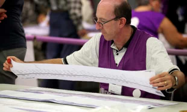 A polling official checks a ballot paper from the WA Senate rerun at an AEC counting centre at Belmont, Perth.