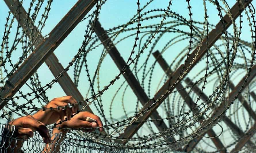 Iraqi detainees rest their hands on razor wires as they watch a group of freed prisoners leaving the Abu Ghraib prison on the outskirts of Baghdad, 16 September 2004.