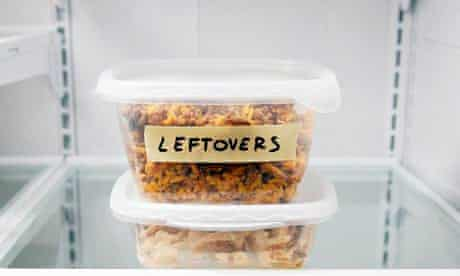 """A plastic tub in on the fridge shelf, labelled """"leftovers"""""""