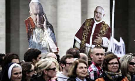 Cut-outs of Pope John Paul II and Pope John XXIII are held aloft by pilgrims