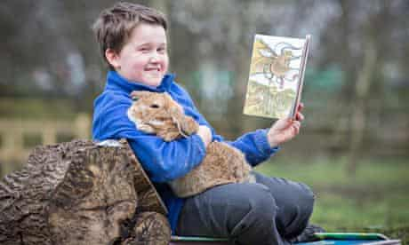 schoolboy reads to pet rabbit
