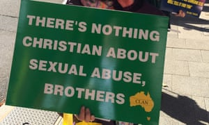 A woman holds a placard outside the royal commission in Perth on Tuesday