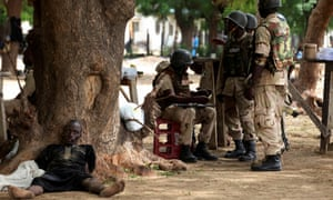 Suspected Islamist sect member captured by Nigerian troops as he lies next to a tree in Maiduguri, Nigeria.
