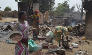 Women gather cooking ingredients in front of a burnt-out house in Mainok, outside Maiduguri, Borno State in March 2014 after at least 74 people were killed in attacks blamed on Boko Haram militants.