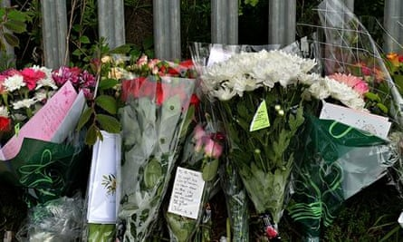 Floral tributes are placed under a pictu