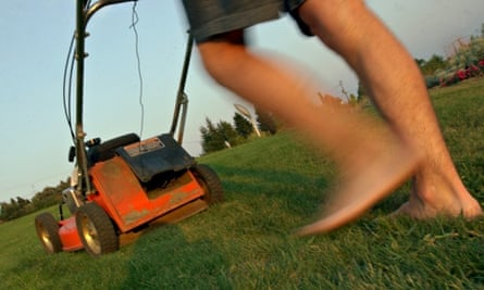 Legs of a barefoot man pushing an old lawn mower on long grass