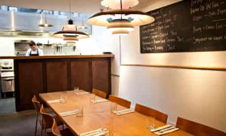 Long table at Artusi with hanging lamps and chalkboard