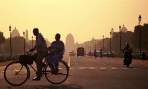 A couple on a bicycle pedal past the Capital building in New Delhi India at sunset