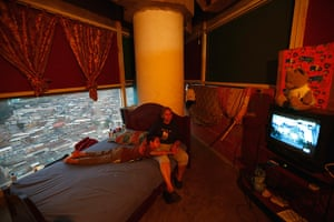 Tower of David: Adriana Gutierrez and her son Carlos Adrian watch TV as they sit on their b