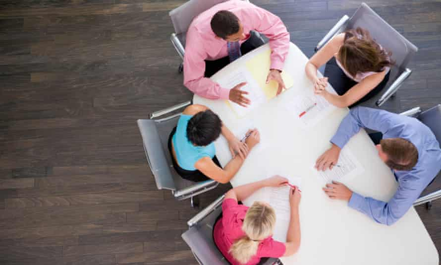 At this office meeting, executives discuss rumors that a photographer has gained unauthorized access to the floor above and is silently watching them through a hole in the ceiling.