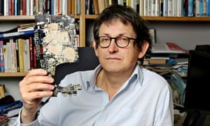Guardian editor Alan Rusbridger holds a piece of one of laptops containing the Edward Snoden files
