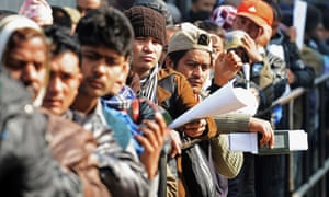 Nepalese migrant workers queue in Kathmandu to receive official documents allowing them to work abroad.