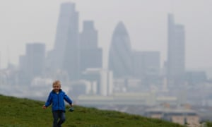 A boy plays as a haze of pollution sits over the London skyline. The pollution is expected to clear on Friday