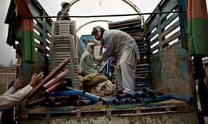 Afghans load up a truck with election materials to be delivered to polling centres in Khost province