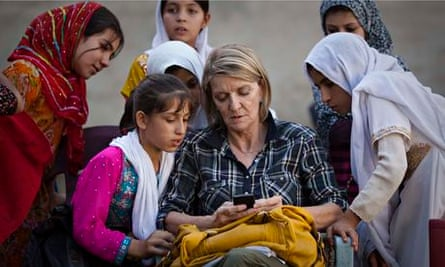 AP journalist Kathy Gannon sits with girls at a school in Kandahar, Afghanistan, in 2011