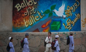 In this March 12, 2014 photo, school children pass by graffiti on the outskirts of Kandahar, southern Afghanistan. Photograph: Anja Niedringhaus/AP