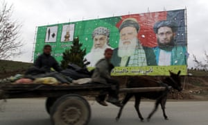 A donkey cart passes electoral billboards in Afghanistan