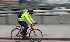 A cyclist wears a mask on London Bridge last week to  guard against Sahara dust.