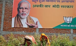 Indian farm workers in front of a Narendra Modi billboard