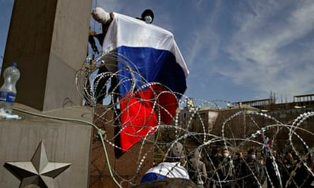 A masked man holds Russian flag above a barricade