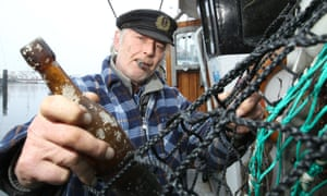 German fisherman Konrad Fischer holds the  message in a bottle from 1913 that was found recently.