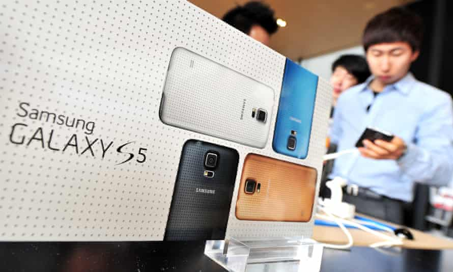 A South Korean customer looks at Samsung's Galaxy S5 smartphone at a mobile phone shop in Seoul on 27 March 2014. Operators offered it for sale early to get around a forthcoming government ban.