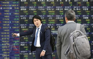 A man points at an electronic stock price indicator as he speaks with his colleague in Tokyo, Tuesday, April 8, 2014