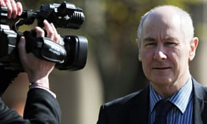 John Darwin in dark suit and tie puts up with a news camera directed on him as he leaves court