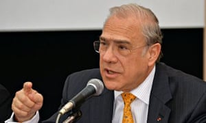 Angel Gurria, in fetching yellow tie and dark suit, gestiulates as he talks at a press conference