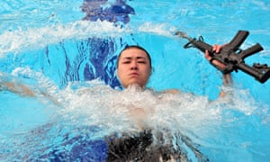 Check out my guns: A US soldier participates in a water survival test during the Best Warrior Competition at Camp Casey in Dongducheon, Seoul.