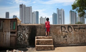 An Indonesian child views the city skyline as he plays at a slum in Jakarta, Indonesia.