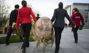 Activists of BUND and Campact ecological associations carry a giant head featuring German Chancellor Angela Merkel before a demonstration against the reform of the Renewable Energy Sources Act (EEG) in front of the chancellery building in Berlin.