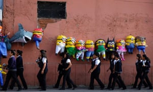 College students walk past below pinatas shaped like Minions from the movie Despicable Me, along a street in downtown Guatemala City.