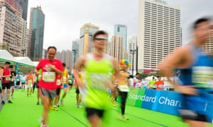 Runners cross the finish line in Victoria Park during the 2013 Hong Kong marathon.