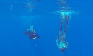Navy divers from the Australian defence vessel Ocean Shield scan the water for debris
