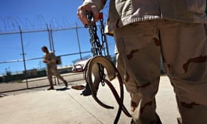 A US military guard carries shackles in Guantánamo Bay