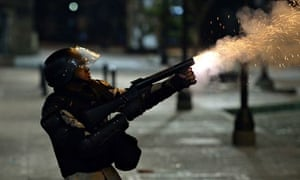 Venezuelan police officer fires teargas at protesters