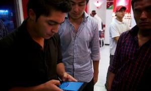 A man checks his email on his smart phone in Kabul's frozen yogurt establishment.