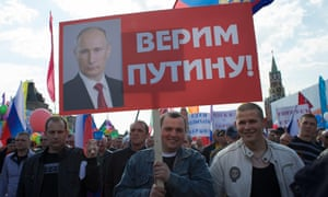 """Red Square. The placards say: """"We Believe in Putin"""" and """"We will spend vacation in Crimea""""."""